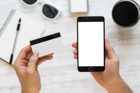 A black smartphone mock up and a credit card in the hands of a man on a rural white background, concepts of Internet commerce