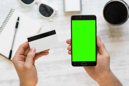 Smartphone with green screen for chroma key compositing and credit card in the hands of a man on a white background, Internet commerce online banking to pay for services and goods in Stock Photo
