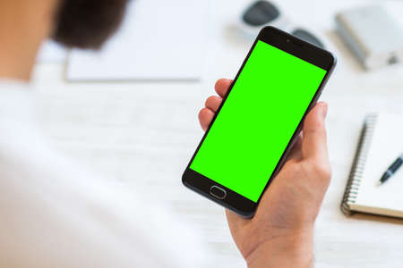 The man uses a smartphone with green screen for chroma key compositing. Concepts of using mobile devices, demos of the site in the mobile version comfort Stock Photo
