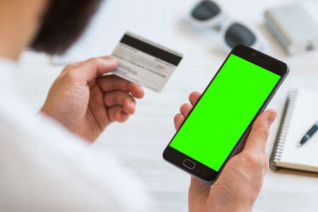 A black smartphone with green screen for chroma key compositing and a credit card in the hands of a man on a rural white background, concepts of Internet commerce and the use of online banking to pay for services and goods in Internet, top view. comfort