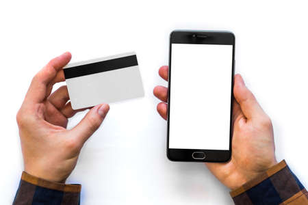 A black smartphone mock up and a credit card in the hands of a man on a rural white background, concepts of Internet commerce and the use of online banking to pay for services and goods in Internet, top view . isolated digital