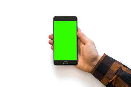 Hand holding black smartphone with green screen for chroma key compositing with blank screen isolated on white background Stock Photo