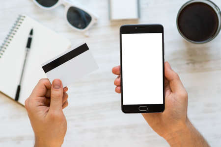 A black smartphone mock up and a credit card in the hands of a man on a rural white background, concepts of Internet commerce and the use of online banking to pay for services and goods in Internet, top view. digital