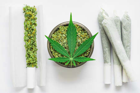 Joint and a grinder with crushed weed Leaf of cannabis, marijuana, unrolled weed on a white background top view close weed Stock Photo
