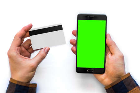A black smartphone with green screen for chroma key compositing and a credit card in the hands of a man on a rural white background, concepts of Internet commerce and the use of online banking to pay for services and goods in Internet, top view isolated comfort Stock Photo
