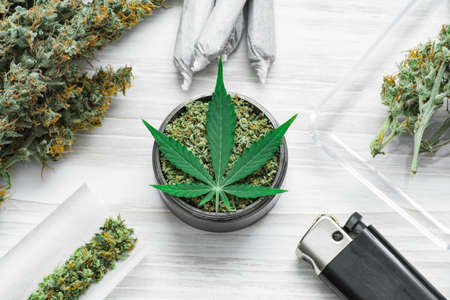 buds of marijuana, grinder with crushed Joint and a weed Leaf of cannabis, unrolled weed on a white wooden background top view medicinal Stock Photo