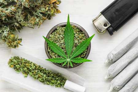 unrolled weed Joint and a grinder with crushed weed Leaf of cannabis, buds of marijuana, on a white wooden background top view medical Stok Fotoğraf