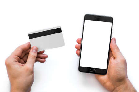 A black smartphone mock up and a credit card in the hands of a man on a rural white background, concepts of Internet commerce and the use of online banking to pay for services and goods in Internet, top view. isolated digital Stock Photo - 95372502