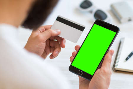 Smartphone with green screen for chroma key compositing and a credit card in the hands of a man on a white background, Internet commerce online banking to pay for services and goods in Internet comfort