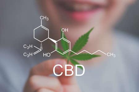 대마 잎을 들고 웃는 아이 아이. 어린이를위한 의약 목적으로 마리 후나를 사용하는 개념, 비 정신 작용 적 칸 나비 디올 CBD 의료의 의료 사용