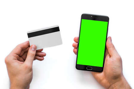 Smartphone with green screen for chroma key compositing and a credit card in the hands man white background, Internet commerce use of online banking to pay goods in Internet, top view. isolated comfort Stock Photo