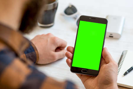 A black smartphone with green screen for chroma key compositing in the hands of a man on a white background, concepts of Internet commerce and the use of online banking to pay for services and goods in Internet. comfort Stock Photo - 95586460