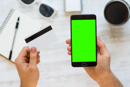 smartphone with green screen for chroma key compositing and a credit card in the hands of a man on white background, Internet commerce online banking to pay for services and goods in Internet comfort