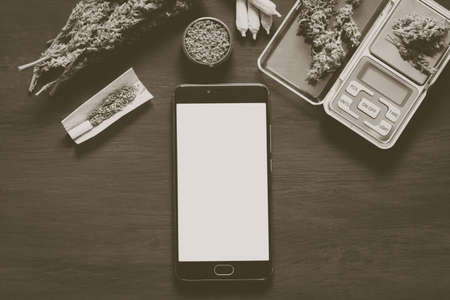 Smartphone with green screen for ?hroma key, chromakey against the background of cannabis flowers, concept online store of herbs of medical marijuana