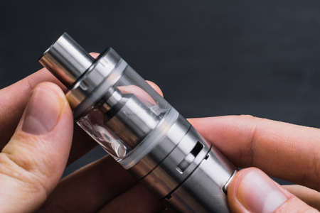 Close-up Man Hand Holding Electronic Cigarette. Imagens