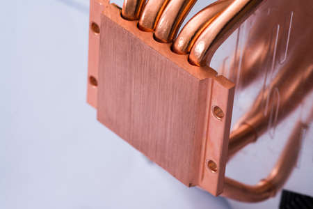 Concept of air cooling of the central processor of a computer Aluminum radiator with copper heat pipe close-up with beautiful bokeh Metallic background Stock Photo