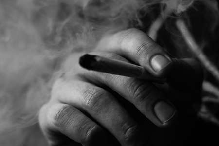 Smoke on a black background. A man smokes cannabis weed, a joint and a lighter in his hands. Concepts of medical marijuana use and legalization of the cannabis.