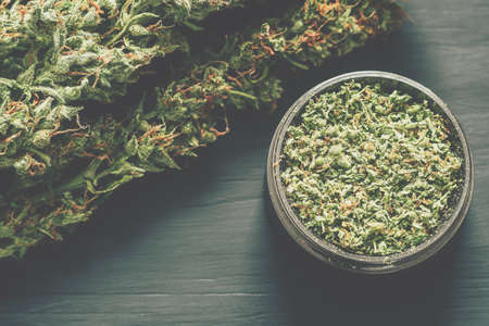 Macro of marijuana with trichomes and crushed grass in a grinder for chopping a canapis on a black table Stock Photo