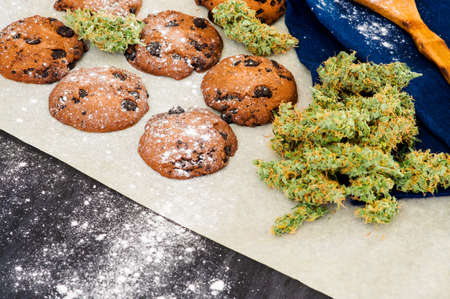 Cookies with cannabis and buds of marijuana on the table. Concept of cooking with cannabis herb. Treatment of medical marijuana for food use, On a black background CBD use Stock Photo