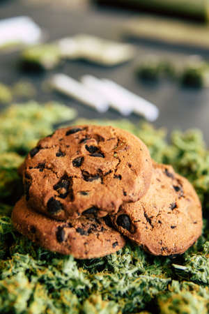 Cookies with cannabis and buds of marijuana on the table. Concept of cooking with cannabis herb. Treatment of medical marijuana for use in food, On a black background close up