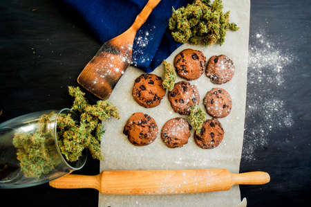 Cookies with cannabis and buds of marijuana on the table. top viewConcept of cooking with cannabis herb. Treatment of medical marijuana for use in food top view, On a black background CBD use