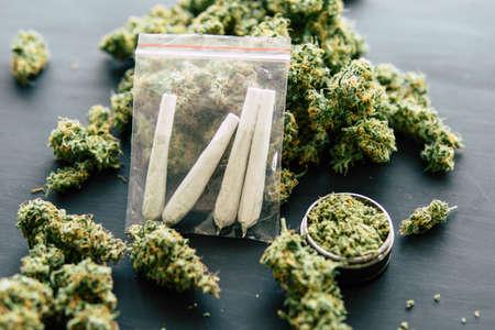 Junta de jamba enrollada en manos de un hombre marihuana y molinillo de marihuana, conceptos de fumar marihuana, fondo oscuro de cerca, vista superior de cerca