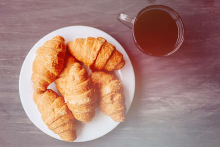 Coffee cup and fresh baked croissants on wooden background. Top View.