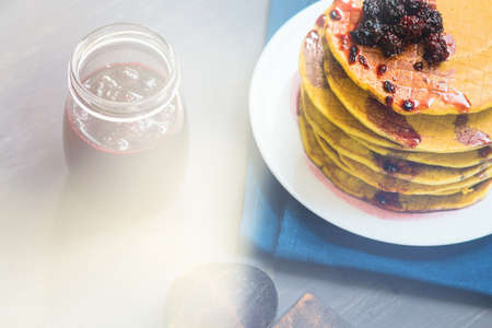 Delicious golden pancakes with fresh blackberries and blackberry jam.