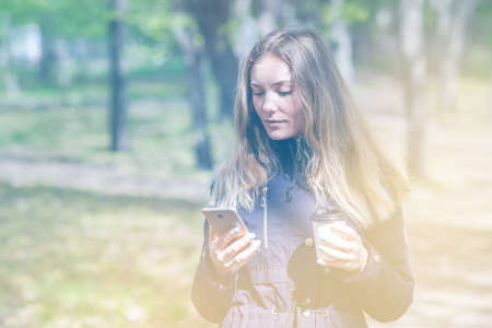 A girl is walking in the morning in a park with a smartphone and coffee Stock Photo