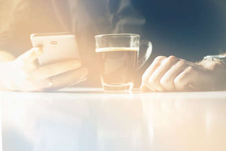 Young man having morning coffee and reading news in his smartphone Stock Photo