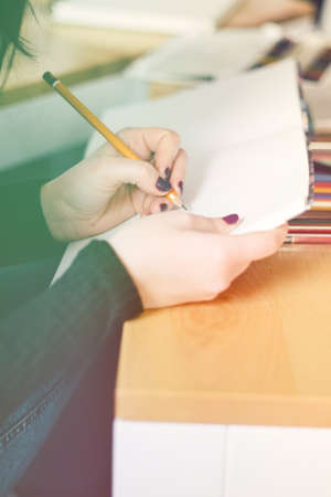 Cropped image of hand of young woman taking notes Stock Photo