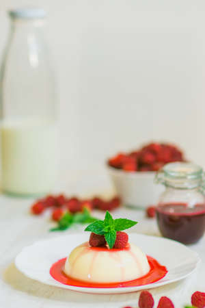 Summer dessert. Close up. Light background. Panakota with raspberries. Vertical shot.