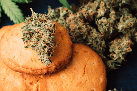 Baking with the addition of CBD. Sweets with weed. Cookies with marijuana. Sweets with cannabis. Cannabis buds on a black background.