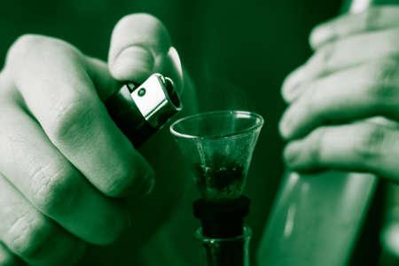 A man smokes bong cannabis weed. Smoke on a black background. Concepts of medical marijuana use and legalization of the cannabis. On a black background