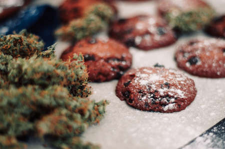 Sweets with cannabis. Cannabis buds on a black background. Baking with the addition of CBD. Sweets with weed. Chocolate cookies with marijuana.