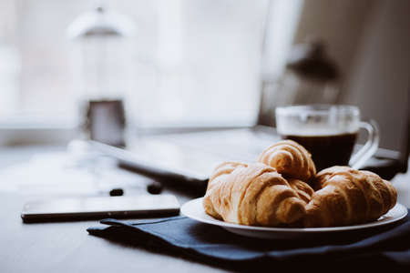 Macro shot of Smartphone and Laptop fresh croissants and coffee black background. Mate moody color. concept of work. Close up.