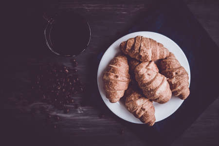 Mate moody color. concept of breakfast. Dessert and coffee beans. Top view. Macro shot of fresh croissants and coffee on a black background.