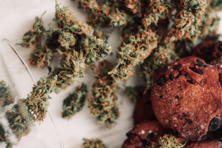 Baking with the addition of CBD. Sweets with weed. Chocolate cookies with marijuana. Sweets with cannabis. Cannabis buds on a black background.
