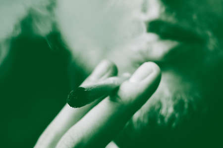 Smoke on a black background. A man smokes cannabis weed, a joint and a lighter in his hands. Concepts of medical marijuana use and legalization of the cannabis. On a black background