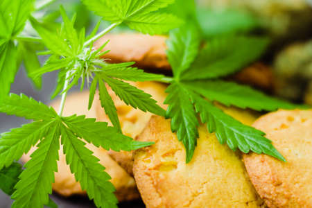 Cookies with marijuana. Sweets with cannabis. Cannabis buds on a black background. Baking with the addition of CBD. Sweets with weed.