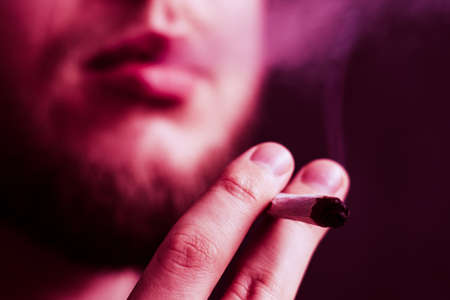 cannabis weed, a joint in his hands A man smokes . Smoke on a black background. Concepts of medical marijuana use and legalization of the cannabis. On a black background Stock Photo