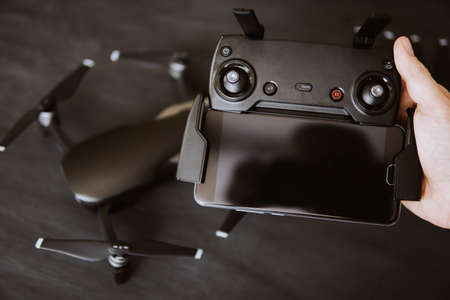 The concept of using drones in life and industry. Innovation photography concept. Mate color. Remote with antennas and a smartphone to control the drone in the hands.