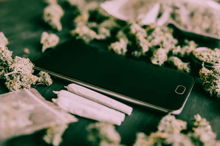 Smartphone and Marijuana Cannabis buds in the package on the table and joint on table in a moody green tone horizontal