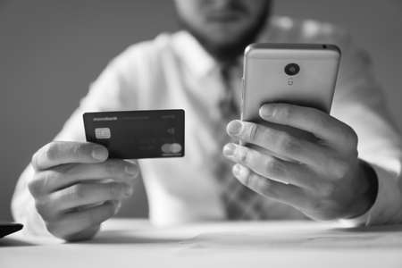 Young businessman with a bank credit card in his hands. Online payments through the phone. Online trading on the currency exchange. Smartphone and Internet Commerce. Payment of goods online.