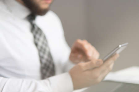 Businessman work with computer on table in office work. Financial business. Light background. Office work with a laptop. Smartphone in hand. Close up. Young bearded businessman.