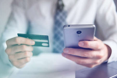 Online trading on the currency exchange. Smartphone and Internet Commerce. Payment of goods online. Online payments through the phone. Young businessman with a bank credit card in his hands. Stock Photo
