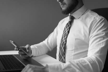 Financial business. Light background. Young bearded businessman. Office work with a laptop. Businessman work with computer on table in office work. Holding smartphone in hand. Stock Photo