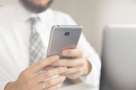 Payment online. Young businessman Smartphone in his hands. Smartphone and Internet Commerce. Online payments through the phone. Online trading. Stock Photo