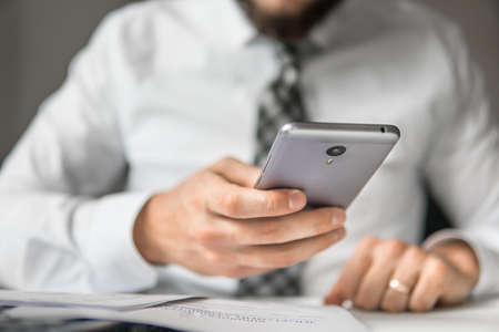 Holding smartphone in hand. Office work with a laptop. Financial business. Light background. Businessman work with computer on table in office work.