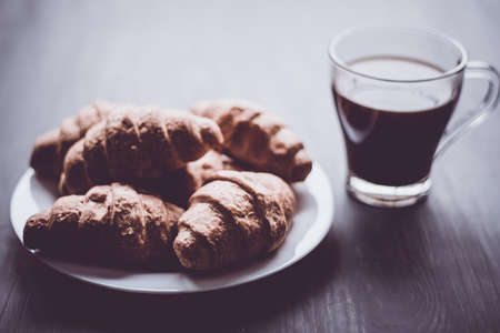 American coffee and fresh croissants on a black background. The concept of breakfast. Dessert and coffee. Mate moody color. Close up. Stock Photo